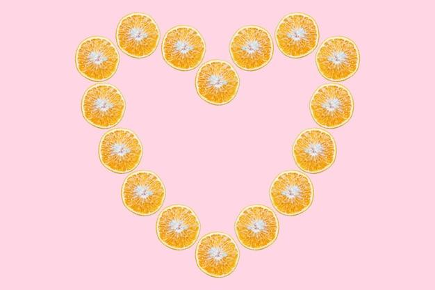 Frutas laranja em forma de coração na superfície do rosa pastel.