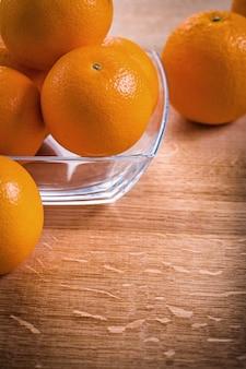 Frutas laranja na tigela quadrada de vidro na mesa de madeira