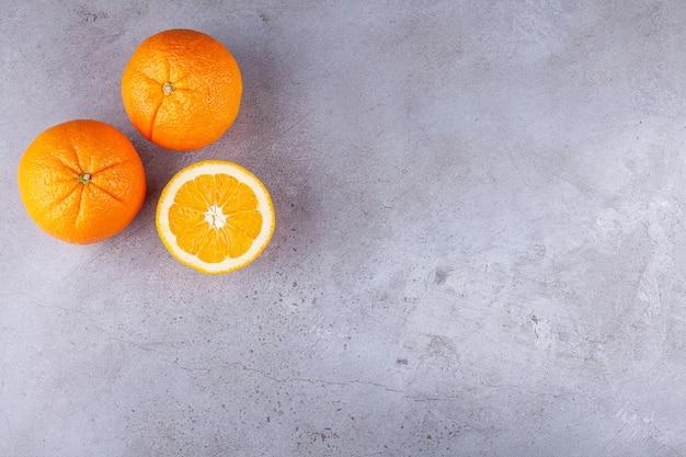 Frutas laranjas inteiras e fatiadas colocadas sobre um fundo de pedra.