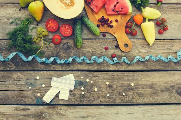 Frutas, legumes, fita métrica, pílulas em fundo de madeira.