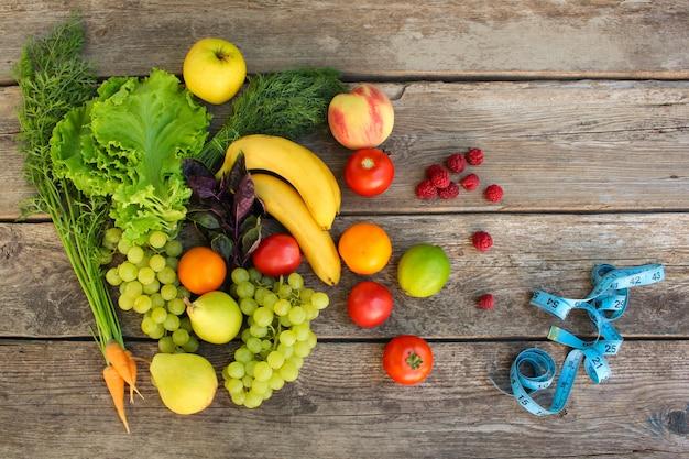 Frutas, legumes, medida de fita em fundo de madeira.