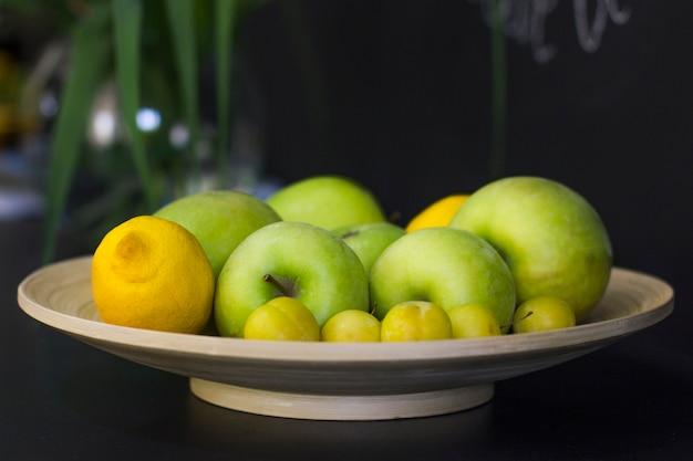 Frutas - limões, maçãs verdes e ameixas amarelas em uma bandeja em uma mesa de madeira preta