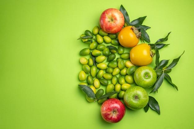 Frutas maçãs caquis frutas cítricas com folhas na mesa