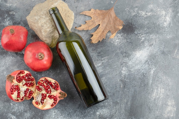 Frutas maduras da romã com uma garrafa de vinho no fundo de mármore.