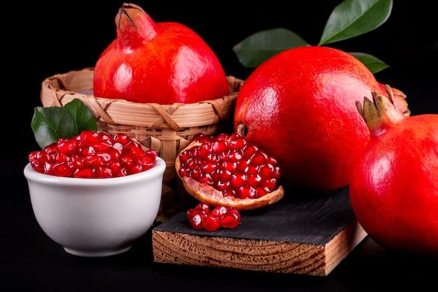 Frutas maduras de romã na mesa de madeira