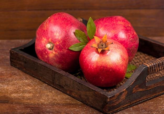 Frutas maduras de romã no fundo de madeira