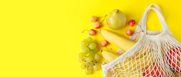 Frutas maduras em um saco de malha em um fundo amarelo saco de cordão de algodão ecofriendly para compras