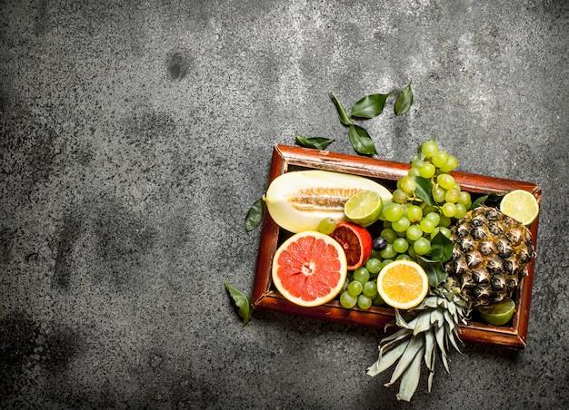 Frutas maduras na velha bandeja na mesa rústica.