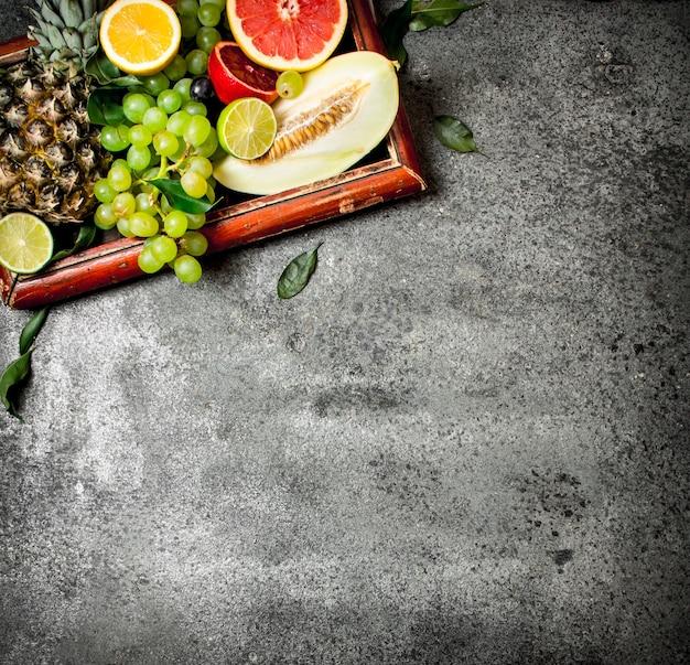Frutas maduras na velha bandeja. sobre fundo rústico.