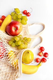 Frutas maduras orgânicas em uma bolsa de malha ecológica em um fundo branco bolsa moderna para compras
