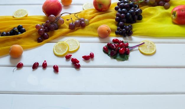 Frutas misturadas em um lenço amarelo sobre uma mesa branca, vista de canto.