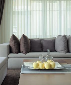 Frutas na bandeja com sofá bege na sala de estar
