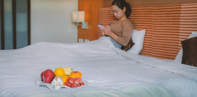 Frutas na bandeja na frente de turistas usaram smartphone na cama no quarto do hotel de luxo.