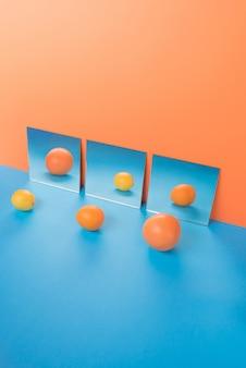 Frutas na mesa azul isolada em laranja perto de espelhos
