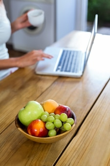 Frutas na mesa com a mulher trabalhando no laptop