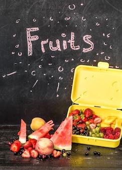 Frutas na mesa preta com inscrição na lousa