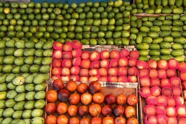 Frutas no balcão de uma pequena loja de rua - maçãs, manga e romã. foto