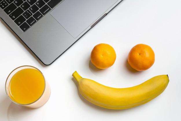 Frutas no local de trabalho. carinha engraçada. laptop, banana, mandarinas e suco de laranja