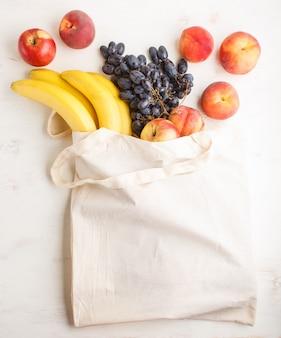 Frutas no saco de têxteis de algodão reutilizável branco sobre fundo branco de madeira.