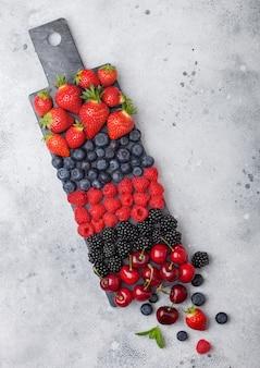 Frutas orgânicas frescas de verão se misturam na placa de mármore preta sobre fundo claro de mesa de cozinha. framboesas, morangos, mirtilos, amoras e cerejas. vista do topo