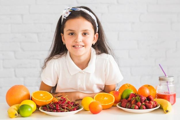Frutas orgânicas frescas na frente da garota feliz