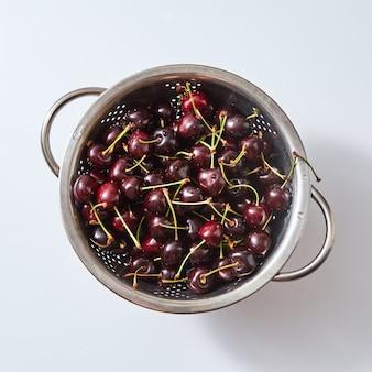 Frutas orgânicas naturais, bagas - grupo de cereja vermelha escura suculenta madura na peneira com gotas de água em um fundo de papel branco. vista do topo.