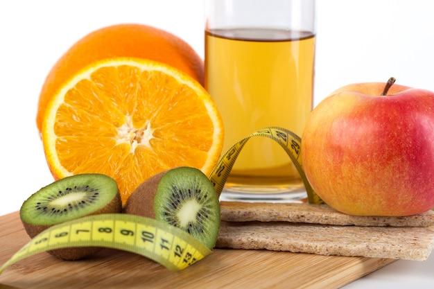 Frutas, ovos, laranja, suco de maçã na placa de madeira com medida isolada no branco
