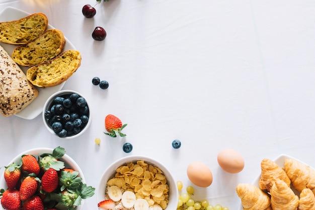 Frutas; pão assado e croissant em fundo branco