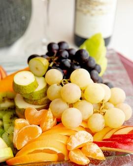 Frutas prato uva laranja kiwi maçã vista lateral