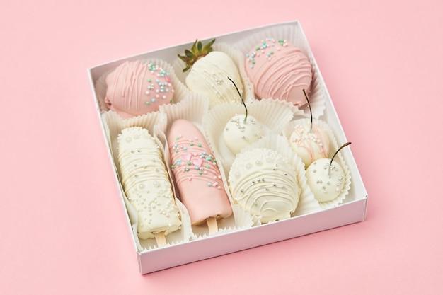 Frutas revestidas com chocolate branco e rosa estão em uma caixa de presente