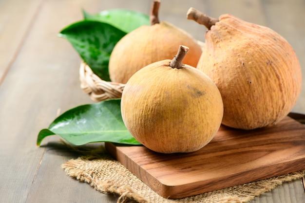 Frutas santol em uma cesta de bambu com fundo de madeira, santol tem gosto azedo e o meio de santol é mais doce. é uma fruta muito famosa da província de lopburi. tailândia