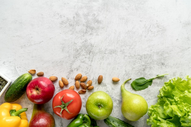 Frutas saudáveis e frescas; legumes e amêndoas sobre superfície texturizada de cimento branco