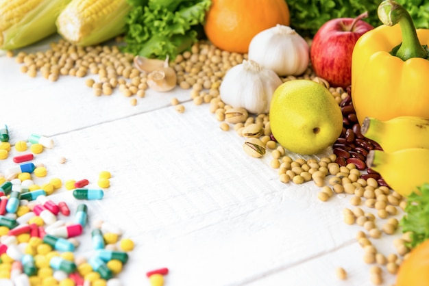 Frutas saudáveis, legumes, temperos e nozes em madeira branca com medicamento