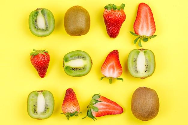 Frutas sazonais de verão tropical suculento maduro manga coco kiwi bananas morangos em fundo amarelo.