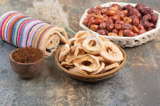 Frutas secas com cacau em pó em tigela de madeira com fundo de mármore. foto de alta qualidade