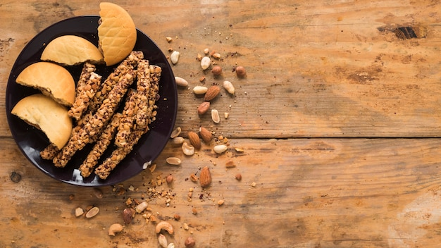 Frutas secas; cookies e barra de granola no plano de fundo texturizado de madeira