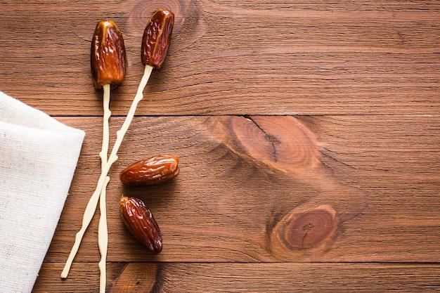 Frutas secas doces colocadas em palitos para comer em uma mesa de madeira. vista do topo
