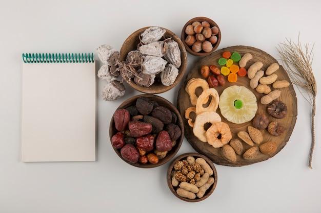 Frutas secas e lanches em várias travessas de madeira e pires com um caderno de lado