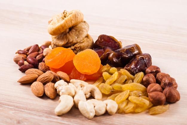 Frutas secas e nozes amontoadas na mesa de madeira