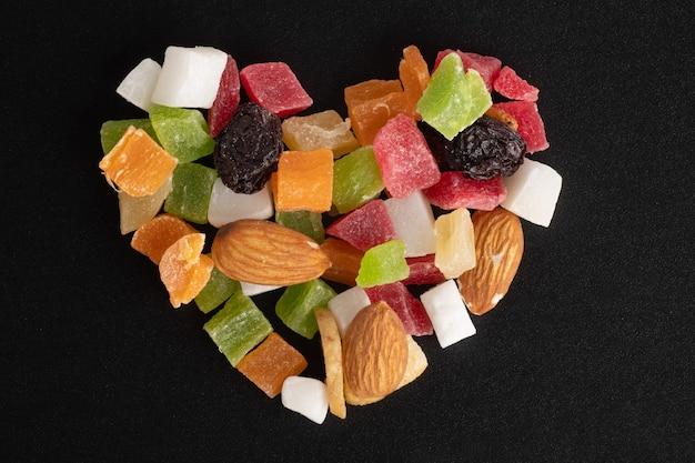 Frutas secas e nozes em forma de coração isoladas em uma superfície preta, vista de cima, close-up, macro