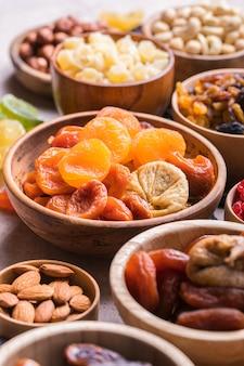 Frutas secas e nozes se misturam em uma tigela de madeira Foto Premium