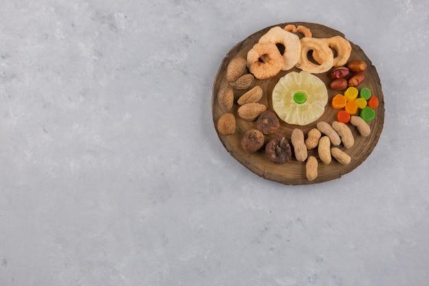 Frutas secas e salgadinhos em travessa de madeira no centro