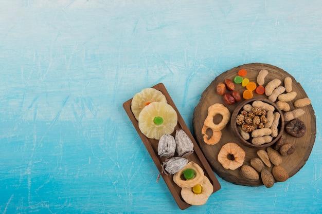 Frutas secas e salgadinhos em travessas de madeira