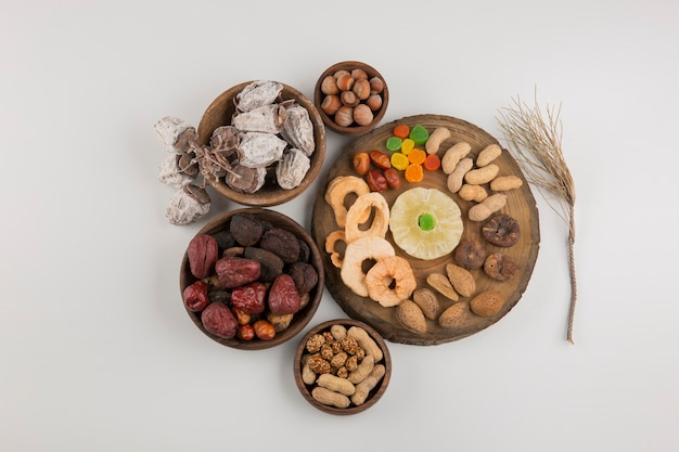 Frutas secas e salgadinhos em várias travessas de madeira e pires no centro