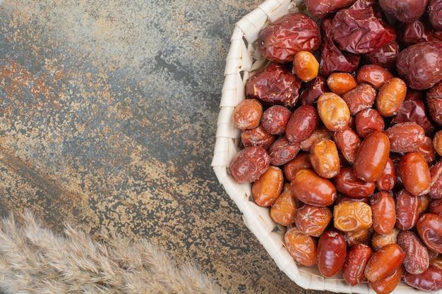 Frutas secas em uma tigela branca sobre fundo de mármore. foto de alta qualidade