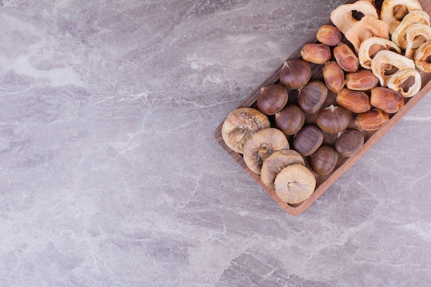 Frutas secas em uma travessa de madeira na pedra
