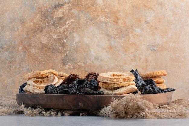 Frutas secas, incluindo fatias de maçã, sultana negra e bagas de jujuba no fundo de concreto.