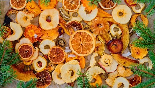 Frutas secas misturadas na mesa de papel, vista superior. delicioso presente, decorado com galhos de árvore de natal. a ideia de café da manhã, lanche saudável. conceito de alimentação saudável ou extração para alimentos