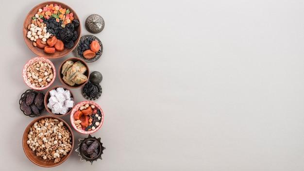 Frutas secas; nozes; datas; lukum e baklava em fundo branco com espaço para escrever o texto