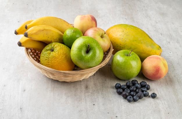 Frutas sortidas em uma cesta sobre a mesa cinza clara.